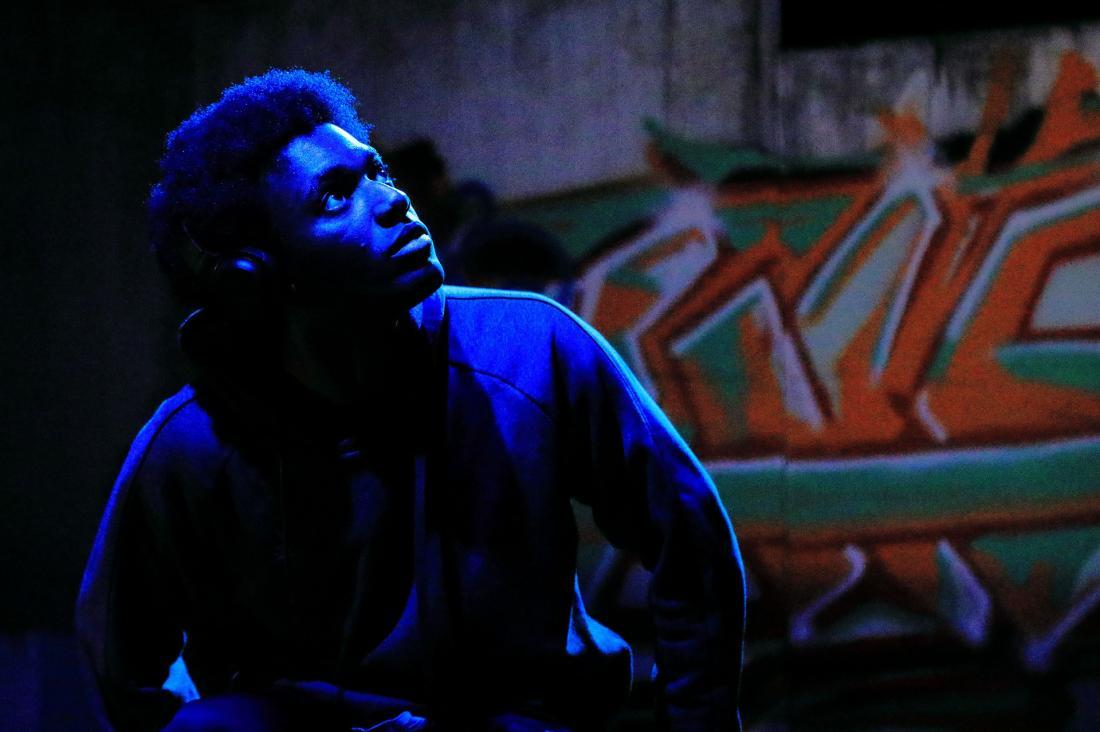 Male sat in blue light in from of graffiti wall
