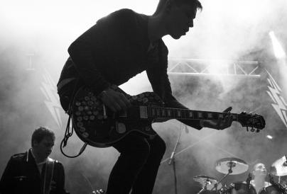 A picture of a guitarist playing in a band