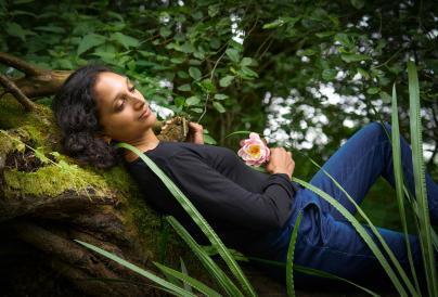 Female laying on tree holding flower