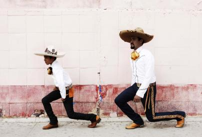 An image of two boys in a sombrero kneeling